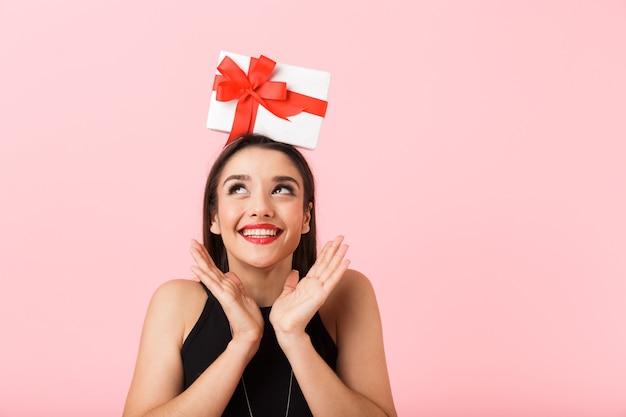 Porträt einer schönen jungen frau, die schwarzes kleid trägt, das lokal über rosa hintergrund steht und geschenkbox auf ihrem kopf hält