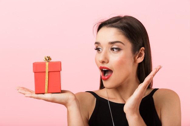 Porträt einer schönen jungen frau, die schwarzes kleid trägt, das lokal über rosa hintergrund steht und geschenkbox hält