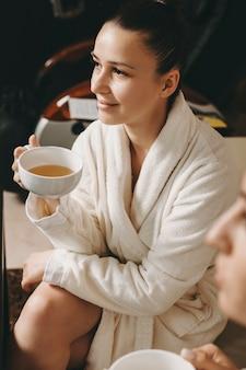 Porträt einer schönen jungen frau, die tee im bademantel in einem wellness-spa-zentrum nach der massage trinkt.