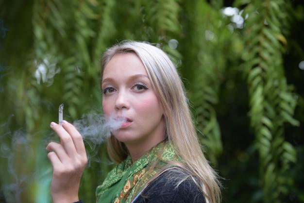Porträt einer schönen jungen frau, die zigaretten raucht. gesundheitsgefahren.