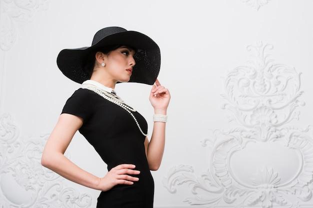 Porträt einer schönen jungen frau im retrostil in einem eleganten schwarzen hut und in einem kleid über luxus-rokoko-weißwand