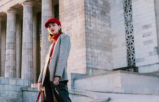 Porträt einer schönen jungen frau in der roten kappe, die vor altem gebäude steht