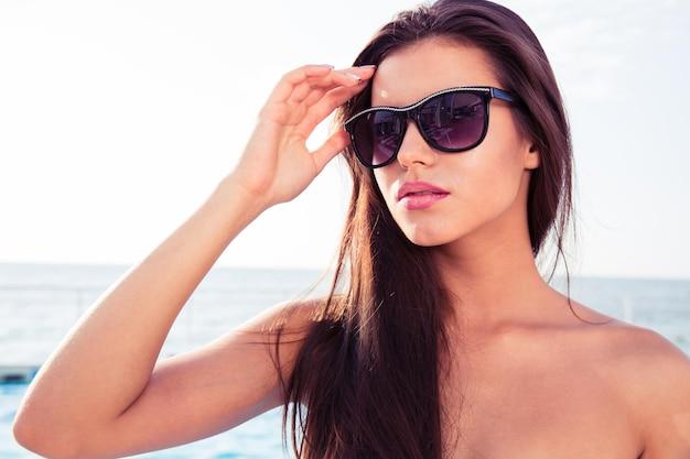 Porträt einer schönen jungen frau in der sonnenbrille, die draußen steht