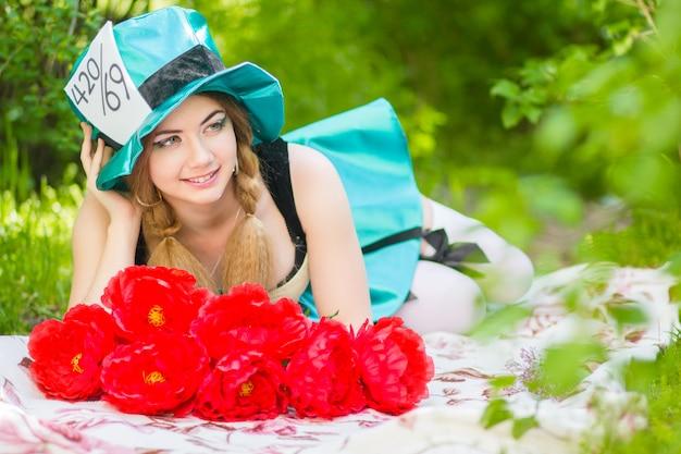Porträt einer schönen jungen frau in einem kostüm des hutmachers in der natur. frau posiert mit einem strauß roter pfingstrosen