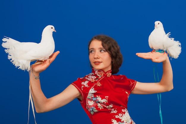 Porträt einer schönen jungen frau in einem roten kleid, in ihren händen zwei weiße tauben