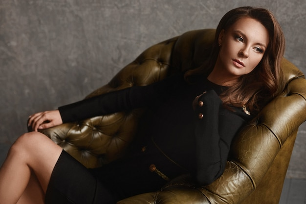 Porträt einer schönen jungen frau in modischen schwarzen kleidern, die in einem vintage-ledersessel sitzen