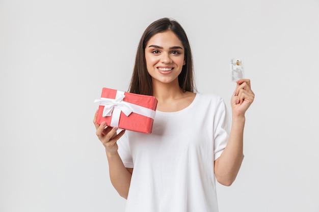 Porträt einer schönen jungen frau lässig gekleidet stehend isoliert auf weiß, geschenkbox haltend, kreditkarte zeigend