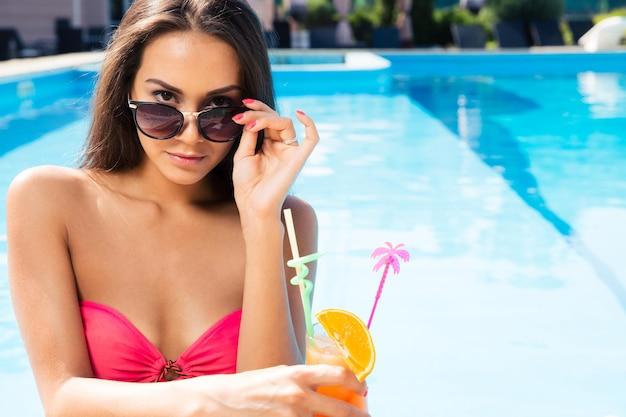 Porträt einer schönen jungen frau mit cocktail im schwimmbad im freien