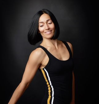 Porträt einer schönen jungen frau mit dem schwarzen haar auf dunkelheit