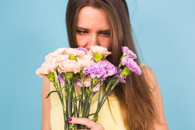 Porträt einer schönen jungen frau mit einem strauß nelken auf blauem hintergrund, feminin, feier