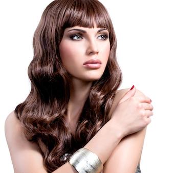 Porträt einer schönen jungen frau mit langen braunen haaren. hübsches mädchenmodell mit stilvoller bijouterie der silbernen farbe.