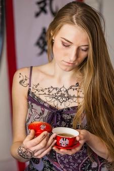 Porträt einer schönen jungen frau mit mehndi tätowierung über ihrem kasten, der in der hand porzellanteeschale betrachtet