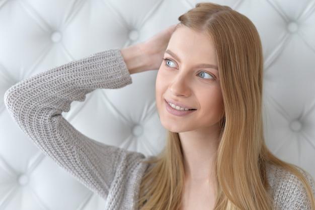 Porträt einer schönen jungen frau mit tiefblauen augen und hand im haar