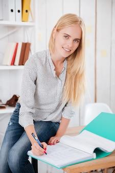 Porträt einer schönen jungen geschäftsfrau, die auf einem schreibtisch sitzt und notizen in dokumenten macht