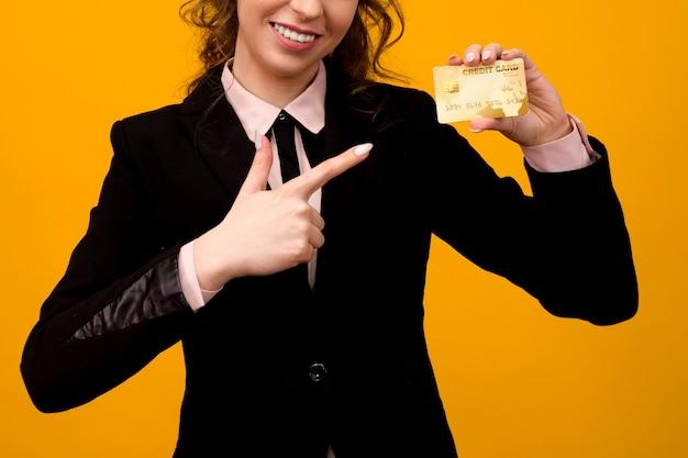 Porträt einer schönen jungen geschäftsfrau, die lokal über gelbem hintergrund steht und kreditkarte hält