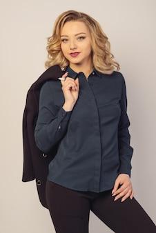 Porträt einer schönen jungen geschäftsfrau, die mit hand hält jacke hinter ihrer schulter gegen grauen hintergrund steht.