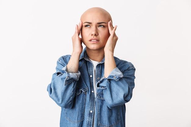 Porträt einer schönen jungen haarlosen frau, die legere kleidung trägt, die isoliert steht und an einer migräne leidet