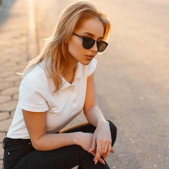 Porträt einer schönen jungen hipsterfrau in der stilvollen sonnenbrille in einem weißen polot-shirt in der schwarzen jeans bei sonnenuntergang. amerikanisches mädchen sitzt auf einer asphaltstraße.
