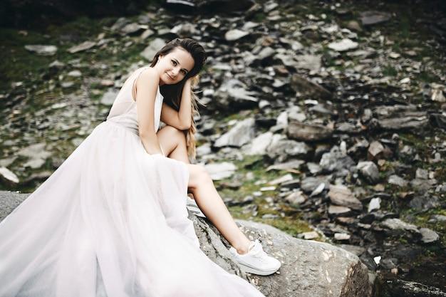 Porträt einer schönen jungen kaukasischen braut mit langen haaren, die kamera betrachten, während sie auf einem felsen in den bergen sitzt und ihren kopf auf ihre lächelnde hand lehnt.