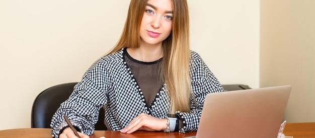 Porträt einer schönen jungen kaukasischen frau, die am tisch sitzt und mit dokumenten arbeitet, die die kamera in einem büro betrachten