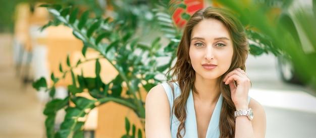 Porträt einer schönen jungen kaukasischen frau, die im blumengarten draußen sitzt