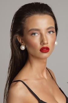 Porträt einer schönen jungen kaukasischen frau mit langen dunklen haaren, schönem make-up, roten lippen im schwarzen badeanzug, mysteriöse blicke auf die kamera