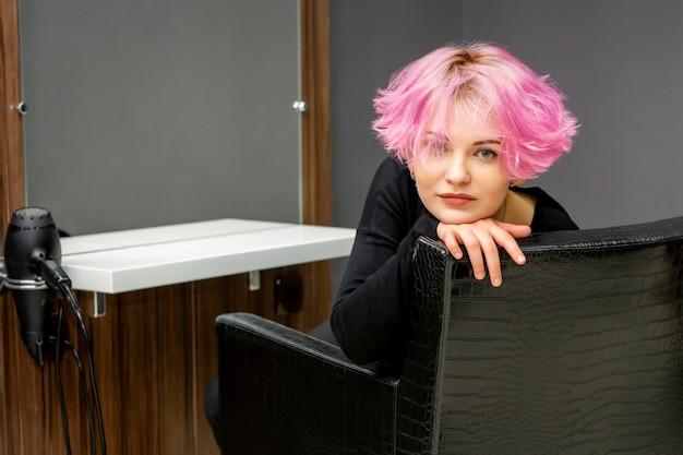 Porträt einer schönen jungen kaukasischen frau mit neuer kurzer rosa frisur, die in einem stuhl an einem schönheitssalon sitzt