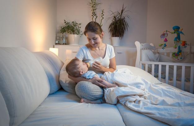 Porträt einer schönen jungen mutter, die ihrem baby nachts im bett milch gibt. elternkonzept