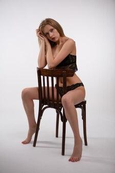 Porträt einer schönen jungen sexy frau, die auf einem stuhl sitzt. foto auf weißer fläche