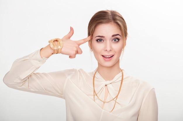 Porträt einer schönen jungen sinnlichen blonden frau im weißen hemd, das mit finger auf seinem kopf schießt und kamera betrachtet.