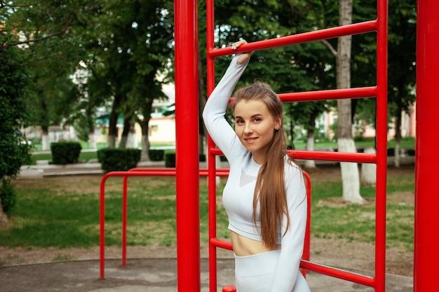 Porträt einer schönen jungen sportlerin. fitness, training, outdoor. trainierter muskulöser körper. park, sportplatz. eine gesunde lebensweise. mädchen lächelt, glücklich