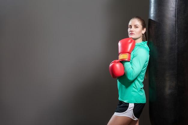 Porträt einer schönen jungen sportlerin mit gesammelten brünetten haaren, die sich in roten boxhandschuhen an einen boxsack lehnen und die kamera betrachten. innenstudio erschossen, auf dunkelgrauem hintergrund isoliert.