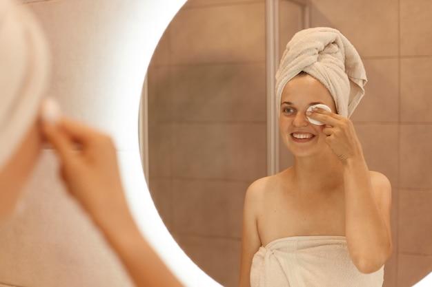Porträt einer schönen kaukasischen frau im handtuch auf dem kopf, die in den spiegel schaut und ihr gesicht mit wattepad säubert, make-up von ihren augen entfernt, lächelt und positiv ausdrückt.