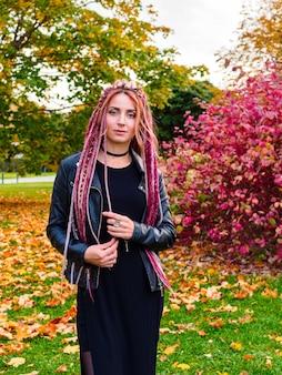 Porträt einer schönen kaukasischen frau mit langen dreadlocks in schwarzer kleidung in einem herbstpark. retuschiertes foto, mittlerer plan