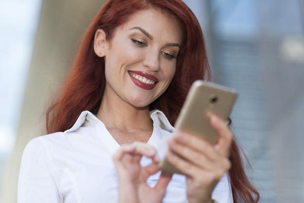 Porträt einer schönen lächelnden frau, die draußen einen handy verwendet