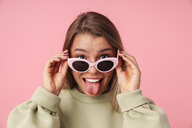 Porträt einer schönen lächelnden frau, die eine sonnenbrille hält und ihre zunge isoliert über rosafarbener wand herausstreckt?