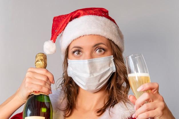 Porträt einer schönen lächelnden frau im weihnachtshut und im kleid, die champagnerglas bei der stellung über grauem hintergrund hält. die frau in der schutzmaske vor dem virus, weihnachten in quarantäne