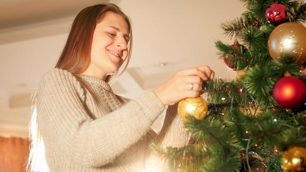 Porträt einer schönen lächelnden frau im wollpullover, die kugeln auf den weihnachtsbaum legt