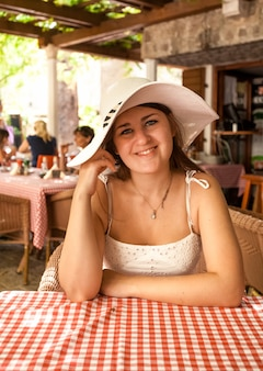 Porträt einer schönen lächelnden frau mit weißem hut, die im restaurant auf der offenen terrasse sitzt