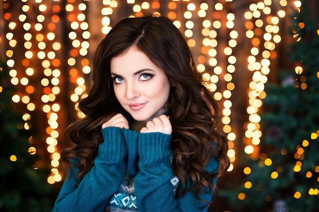 Porträt einer schönen lächelnden frau mit welligem haar auf einem unscharfen weihnachtshintergrund zu hause.