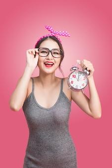 Porträt einer schönen lächelnden jungen asiatischen frau, die wecker zeigt