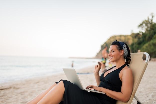 Porträt einer schönen lächelnden jungen frau, die auf dem strand mit laptop sitzt.