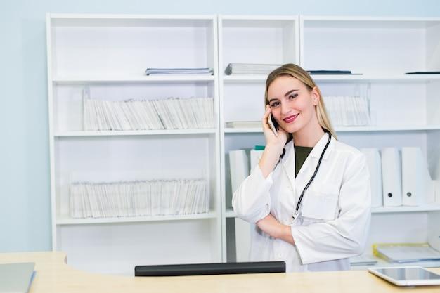 Porträt einer schönen lächelnden krankenschwester an der schreibtischstation beim telefonieren und ausfüllen eines medizinischen informationsformulars