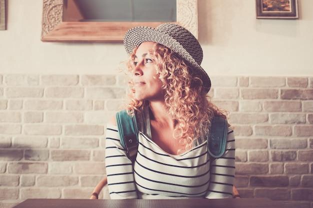 Porträt einer schönen lockigen frau am tisch des restaurants, die denkt und träumt und lächelnd wegschaut
