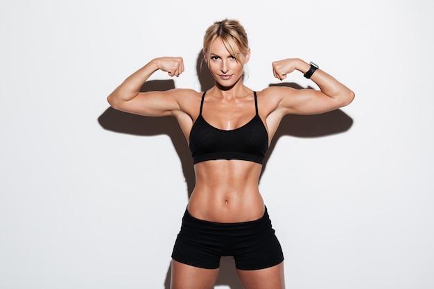 Porträt einer schönen muskulösen sportlerin, die ihre muskeln spannt