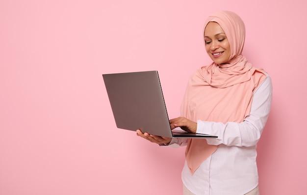Porträt einer schönen muslimischen arabischen frau im rosa hijab, die am laptop arbeitet, lokalisiert auf farbigem hintergrund mit kopienraum. erfolgreiche programmiererin, it-mitarbeiterin, start-up, geschäftsfrau