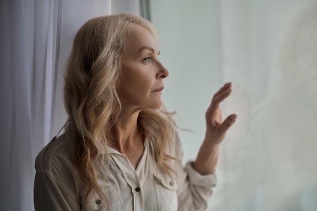 Porträt einer schönen, niedergeschlagenen blonden kaukasischen reifen einsamen frau, die aus dem fenster schaut