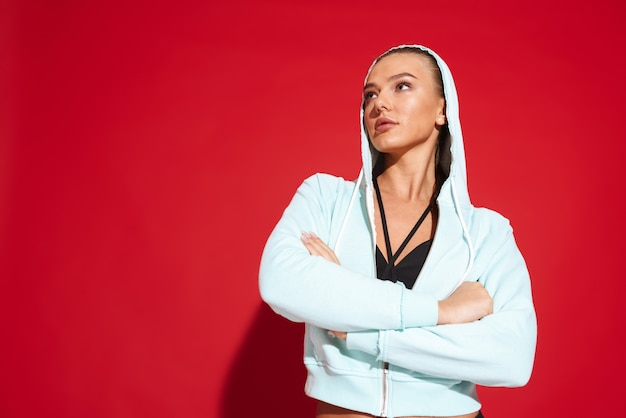 Porträt einer schönen passenden jungen sportlerin, die hoodie stehend trägt
