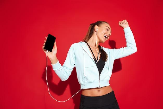 Porträt einer schönen passenden jungen sportlerin stehend, musik mit kopfhörern hörend, handy haltend