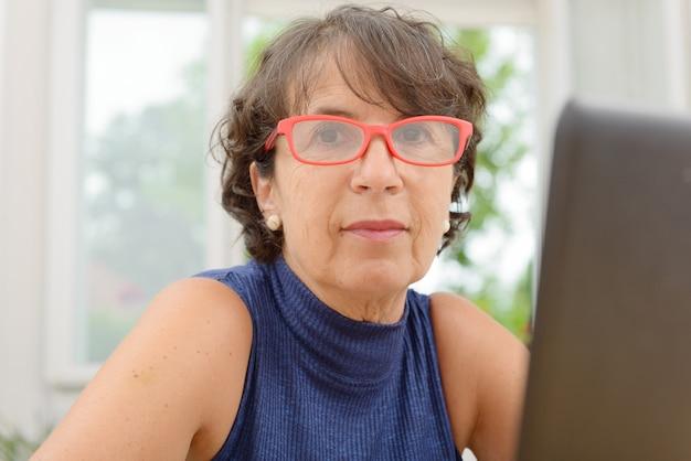 Porträt einer schönen reifen frau mit roten gläsern
